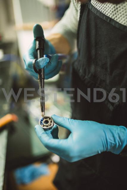 Young mechanic greasing ball bearing, close up - RAEF000796