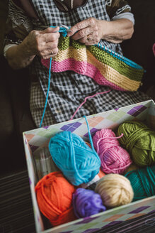 Box of different balls of wool and knitting senior woman - RAEF000806