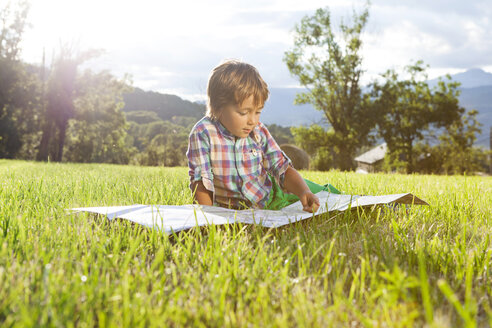 Spain, Cerdanya, little boy on a meadow looking at map - VABF000076