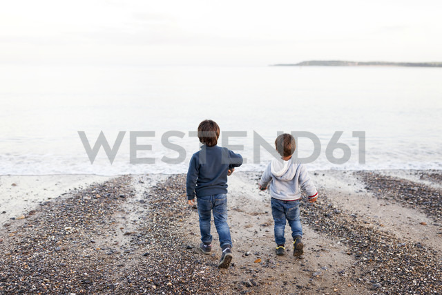 UK, Tenby, back view of two little boys playing at saeshore - VABF000092