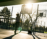 Back view of young woman throwing basketball on a playing field - MADF000775