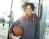 Portrait of smiling young woman with basketball at backlight - MADF000778
