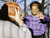 Portrait of smiling young woman passing basketball - MADF000787