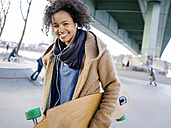 Smiling young woman with longboard hearing music with earphones - MADF000790