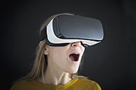 Astonished woman wearing Virtual Reality Glasses - RBF004084