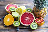 Ananas, blueberries, wolfberries, kiwis and sliced citrus fruits on wood - SARF002493