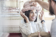 Portrait of woman putting on an old hat in antique shop - ZEF008103