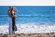 Spain, Tenerife, happy couple standing at seafront of the beach - SIPF000131
