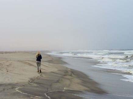 Namibia, Namib desert, woman on beach, freezing cold and stormy - AMF004709