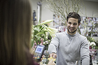 Smiling customer paying in flower shop - ZEF008117