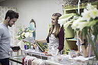 Smiling customer with florist in flower shop - ZEF008120