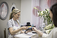 Customer paying in flower shop - ZEF008126