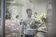 Smiling young man with bunch of flowers leaving flower shop - ZEF008129