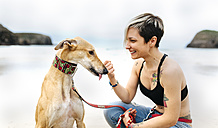 Spain, Llanes, smiling young woman with her greyhound on the beach - MGOF001298