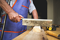 Man with crutch sawing piece of wood on workbench - KIJF000132