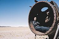 Bolivia, Uyuni train cemetery, man relaxing inside an old train tank - GEMF000665