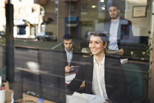 Group of people working at office near to window with young woman smiling - JASF000357