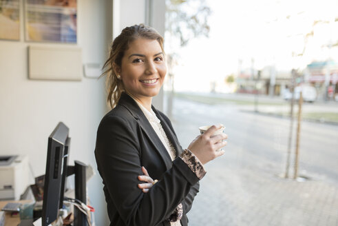 Portrait of smiling young businesswoman at the window - JASF000366
