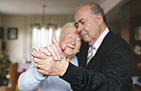 Hands of senior couple dancing together at home - GEMF000675