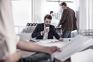 Man sitting at desk drinking coffee in busy office - ZEF008138