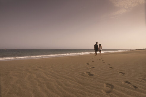 Spain, Tenerife, back view of young couple in love walking on sandy beach - SIPF000147