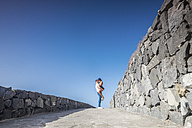 Spain, Tenerife, young couple in love in front of blue sky - SIPF000150