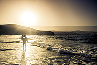Spain, Tenerife, silhouette of young couple in love at seafront - SIPF000153