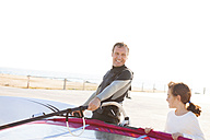Smiling man with daughter at the coast with surfboard - VABF000107