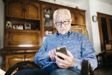 Portrait of senior man using  smartphone at home - JRFF000379