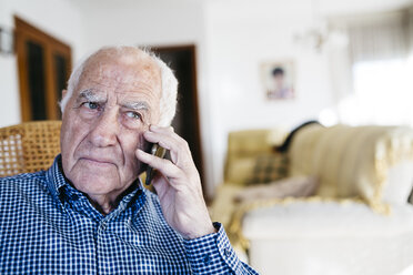Portrait of senior man telephoning with smartphone at home - JRFF000382