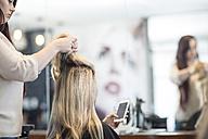 Hairdresser in hair salon checking hair of customer - ZEF008198