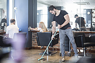 Hairdresser sweeping floor in salon with customers in background - ZEF008213