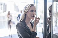Young businesswoman applying lipstick in window reflection - ZEF008231