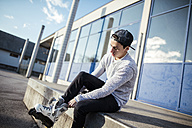 Young man sitting on ramp putting on inline skates - DAWF000487