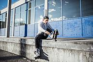 Young man sitting on ramp putting on inline skates - DAWF000490