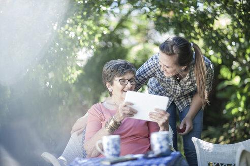 Grandmother and granddaughter in garden together looking at digital tablet - ZEF008280
