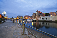 Poland, Bydgoszcz, cityscape at dusk along Brda River with old granaries - ABOF000077