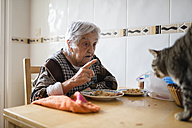 Senior woman sitting at dining table scolding her cat - RAEF000819
