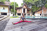 Indonesia, Bali, woman practising yoga at the poolside - KNTF000220