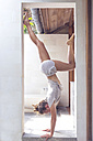 Woman doing a handstand in doorframe - KNTF000226
