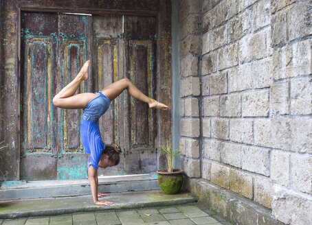 Woman doing a handstand outdoors - KNTF000229