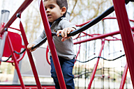 Toddler playing on red playground equipment - VABF000108