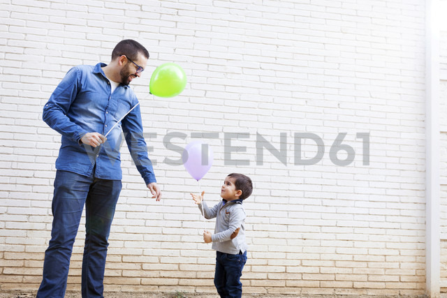 Father and his little son with balloons in front of a white brick wall - VABF000111