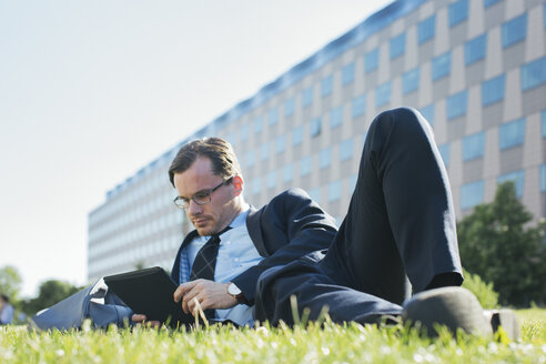 Businessman resting on meadow looking at digital tablet - JUBF000084