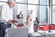 Senior colleagues in office with documents and meeting in background - ZEF008314