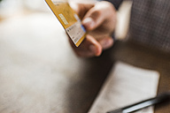 Close-up of hand holding credit card - UUF006403