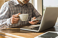 Close-up of man with cell phone and laptop at desk - UUF006412