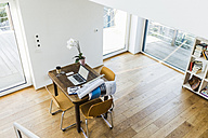 Laptop on wooden desk in an apartment - UUF006415