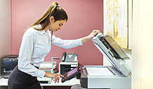 Young businesswoman working at copying machine in the office - MGOF001315