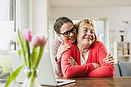 Smiling young woman hugging senior woman at table with laptop - UUF006432